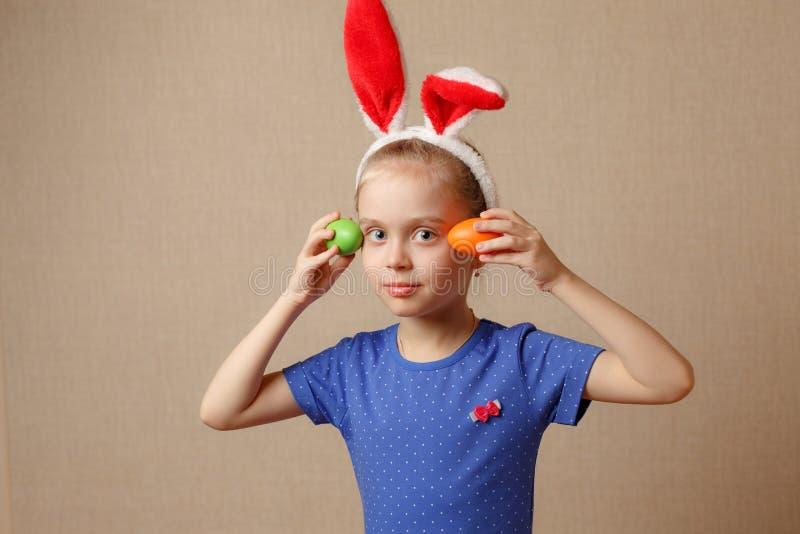 Petite fille mignonne avec des oreilles de lapin et des oeufs de pâques image stock