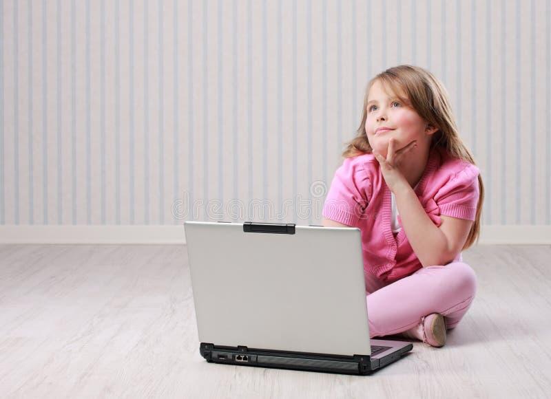 Petite fille mignonne avec l'ordinateur portable images libres de droits