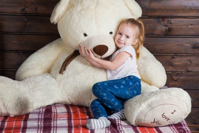 Petite fille mignonne avec l'ours de nounours énorme Je t'aime texte sur à photographie stock