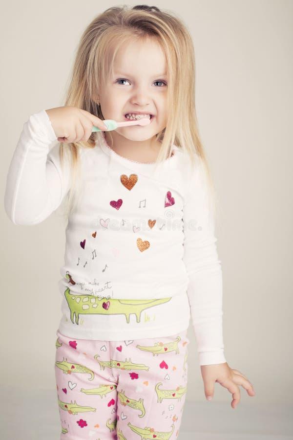 Petite fille mignonne avec la brosse à dents photographie stock