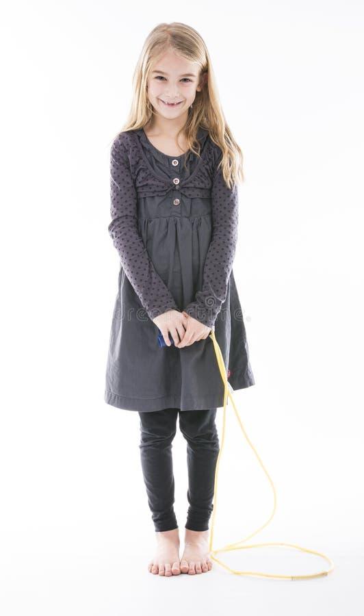 Petite fille mignonne avec la corde à sauter images stock