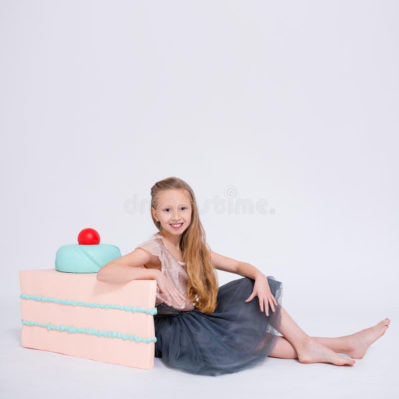 Petite fille mignonne avec la grande tranche de l'espace de gâteau et de copie au-dessus du blanc images libres de droits