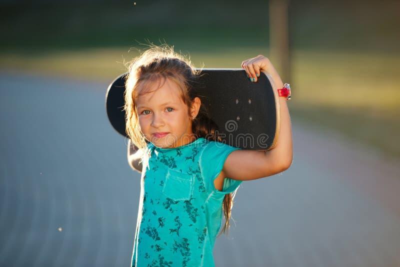 Petite fille mignonne avec la planche à roulettes photos libres de droits