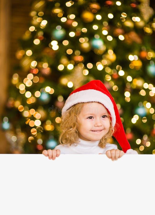 Petite fille mignonne avec le chapeau rouge de Santa tenant le conseil blanc avec l'espace pour le texte photos stock