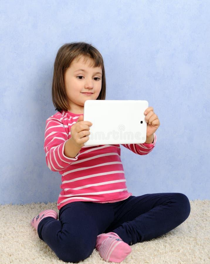 Petite fille mignonne avec le comprimé photographie stock libre de droits