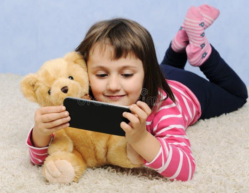 Petite fille mignonne avec le téléphone photos stock