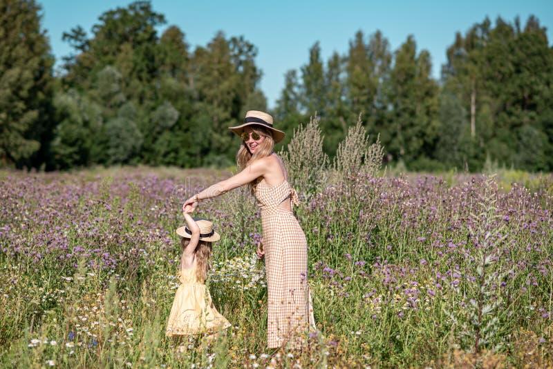 Petite fille mignonne avec sa mère marchant dans le domaine de fleurs photographie stock libre de droits