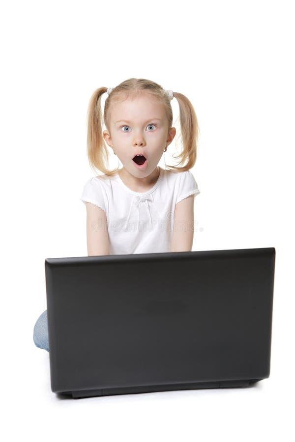 Petite fille mignonne avec un ordinateur images libres de droits