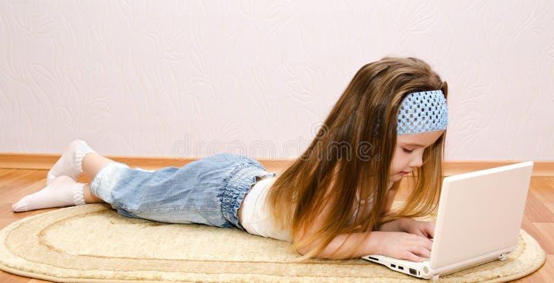 Petite fille avec un ordinateur portable à la maison sur le plancher image libre de droits