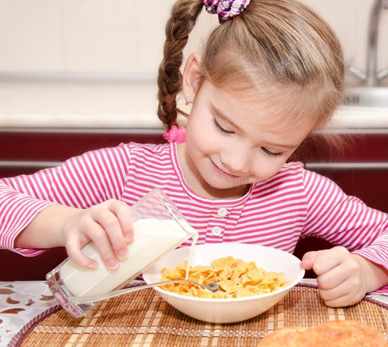 Petite fille mignonne ayant des céréales de petit déjeuner avec du lait images stock