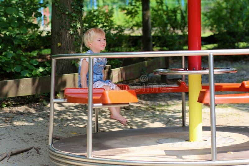 Petite fille mignonne ayant l'amusement au terrain de jeu photographie stock