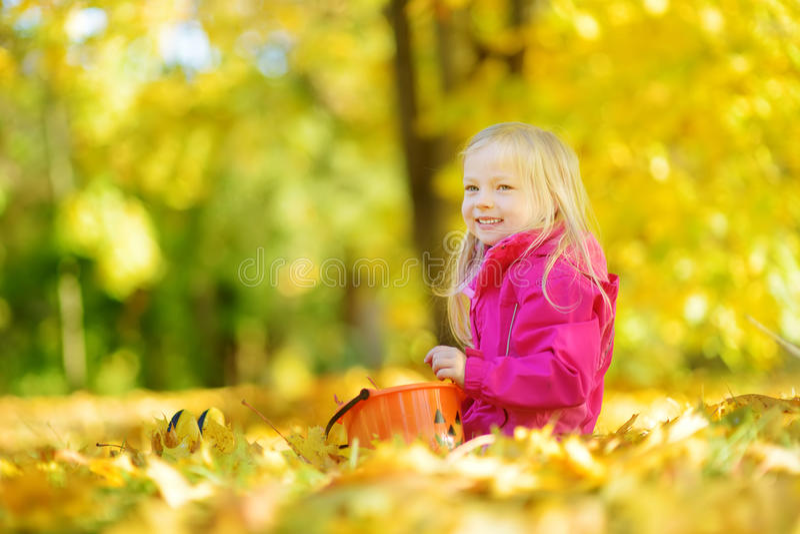 Petite fille mignonne ayant l'amusement le beau jour d'automne Enfant heureux jouant en parc d'automne Enfant recueillant le feui image stock