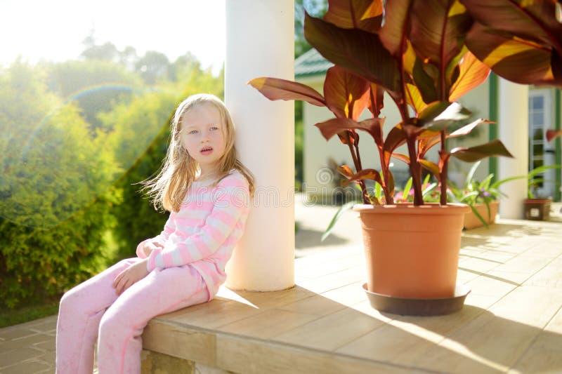 Petite fille mignonne ayant l'amusement sur l'arrière-cour la soirée ensoleillée d'été photo libre de droits