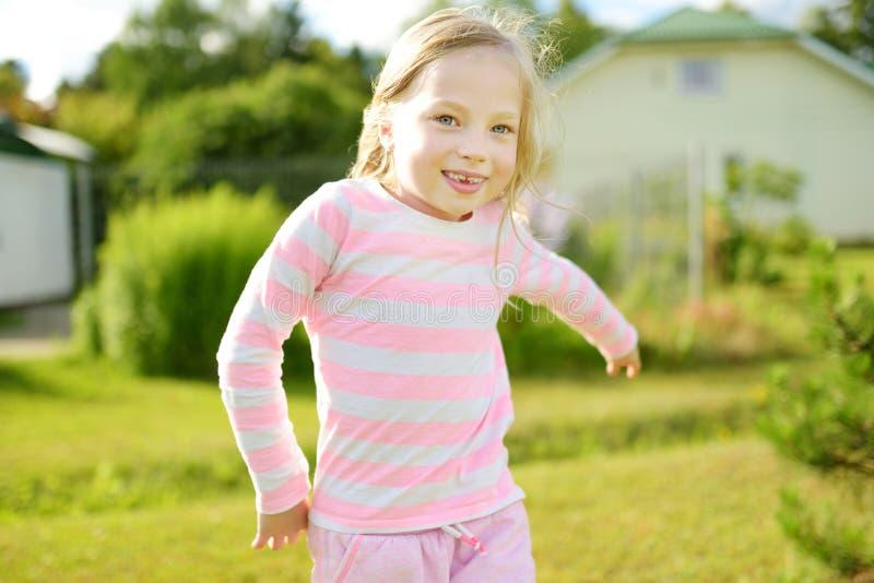 Petite fille mignonne ayant l'amusement sur l'arrière-cour la soirée ensoleillée d'été photographie stock libre de droits