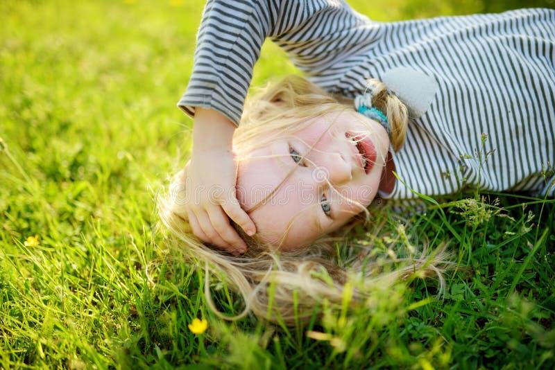 Petite fille mignonne ayant l'amusement sur une herbe sur l'arrière-cour la soirée ensoleillée d'été image stock