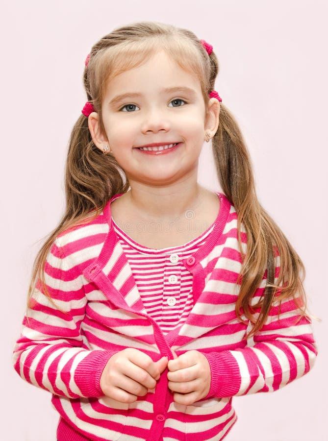 Petite fille mignonne boutonnant sa veste photographie stock