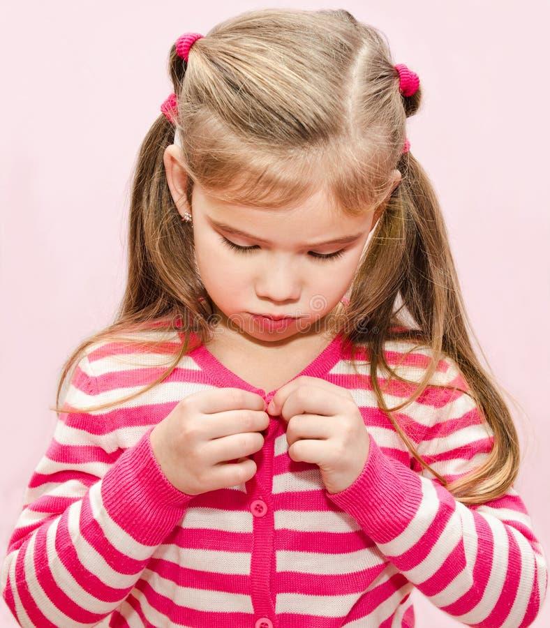Petite fille mignonne boutonnant sa veste image libre de droits