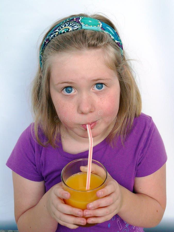 Petite fille mignonne buvant du jus d'orange par un S image stock