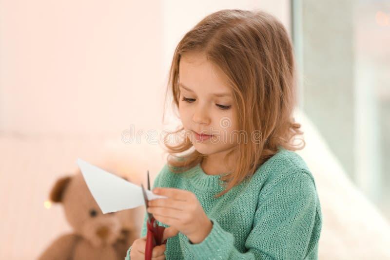 Petite fille mignonne coupant les chiffres de papier photo stock