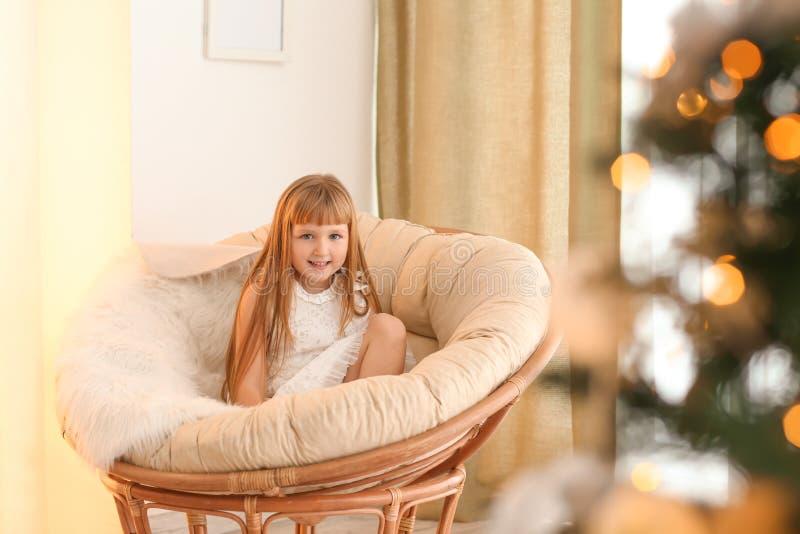 Petite fille mignonne détendant dans la chaise longue le réveillon de Noël photo libre de droits