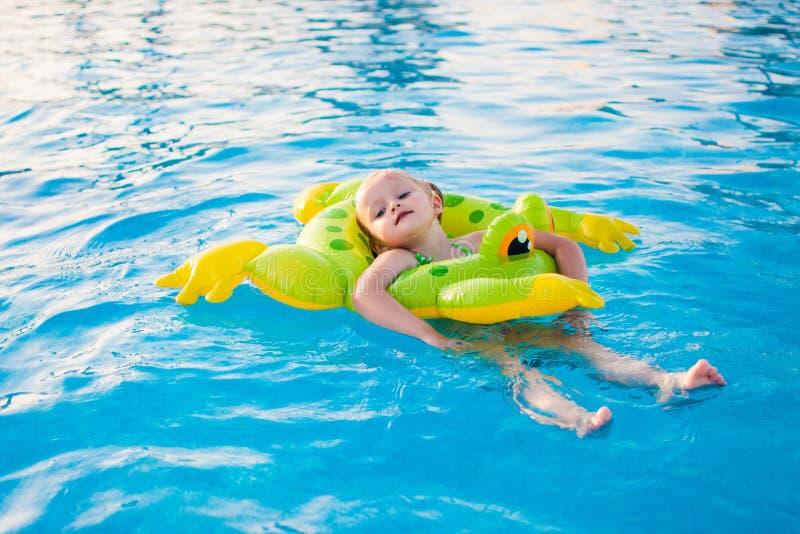 Petite fille mignonne détendant dans la piscine images stock
