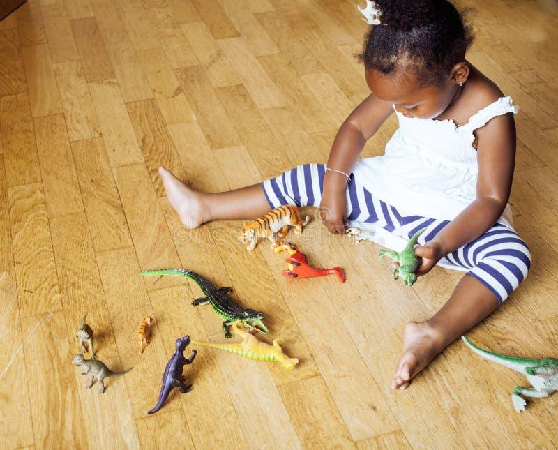 Petite fille mignonne d'afro-américain jouant avec les jouets animaux à la maison, princesse assez adorable dans le sourire heure images stock