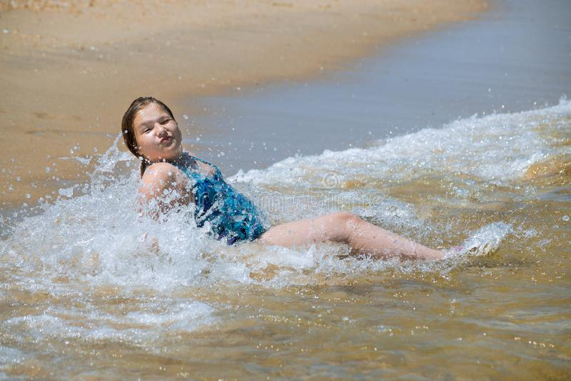 Petite fille mignonne dans beau avec l'eau et le sable se reposant au rivage de s de la mer sur la plage paisible vide photographie stock