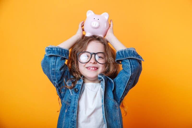 Petite fille mignonne dans des lunettes secouant la boîte porcine sur le fond orange photographie stock