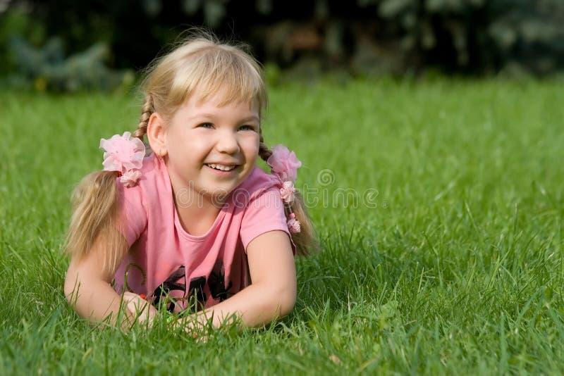 Petite fille mignonne dans l'herbe. photographie stock libre de droits