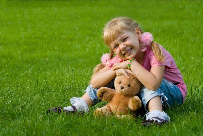 Petite fille mignonne dans l'herbe avec l'ours de nounours. image stock