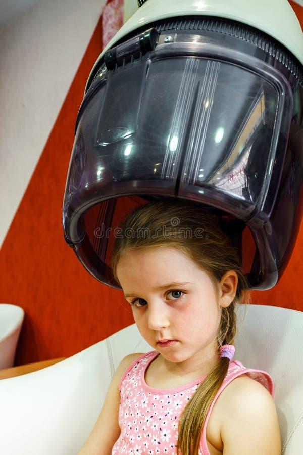 Petite fille mignonne dans la salle de coiffure photo stock