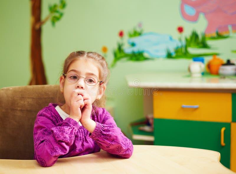 Petite fille mignonne dans le jardin d'enfants pour des enfants avec le besoin spécial photos libres de droits