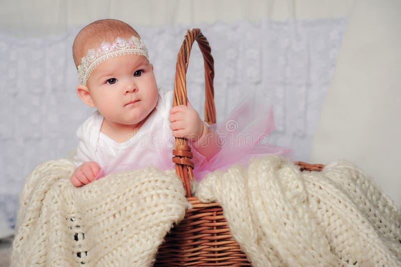 Petite fille mignonne dans le panier avec le bandeau de dentelle photographie stock libre de droits
