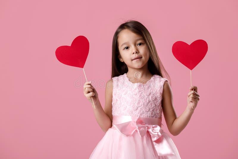 Petite fille mignonne dans une robe rose tenant un coeur de papier images libres de droits