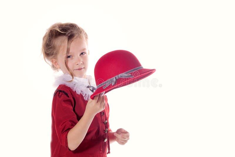Petite fille mignonne dans une robe rouge tenant le chapeau rouge dans des bras Projectile d'isolement de studio images libres de droits