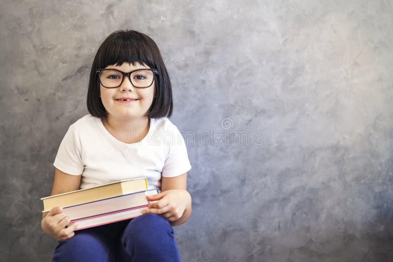 Petite fille mignonne de cheveux noirs avec des verres tenant des livres par le wa photo libre de droits