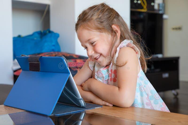 Petite fille mignonne de sourire observant le comprimé numérique dans le salon photographie stock libre de droits