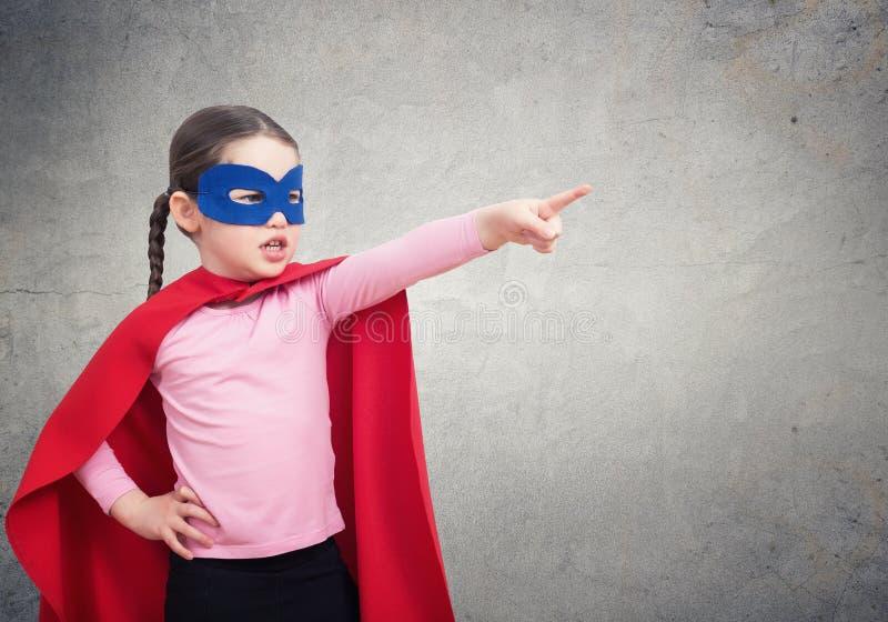 Petite fille mignonne de superhéros dans le manteau rouge contre le mur gris photographie stock libre de droits