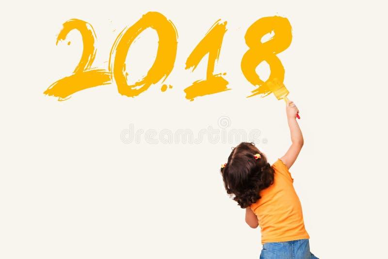 Petite fille mignonne dessinant la nouvelle année 2018 avec la brosse de peinture sur le wa images libres de droits