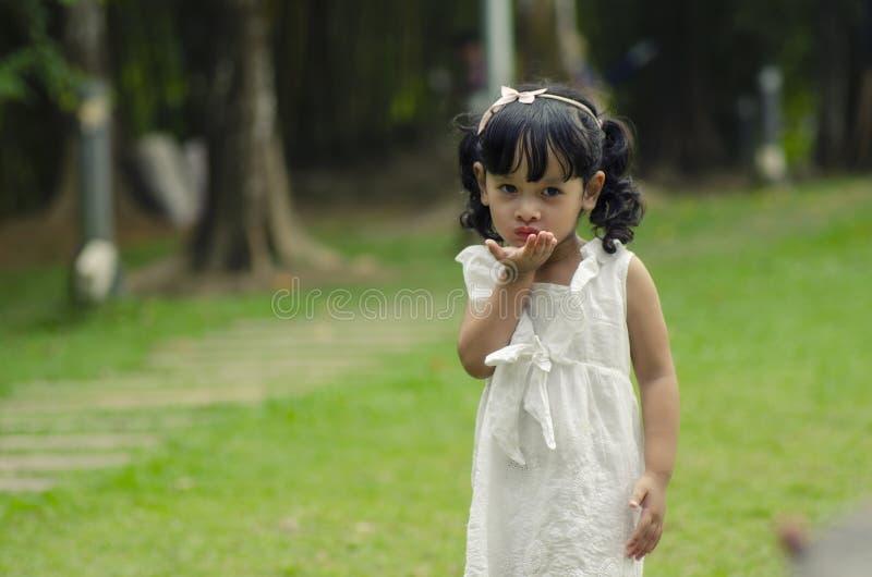 Petite fille mignonne donnant le baiser volant au-dessus de la profondeur du fond de champ image libre de droits