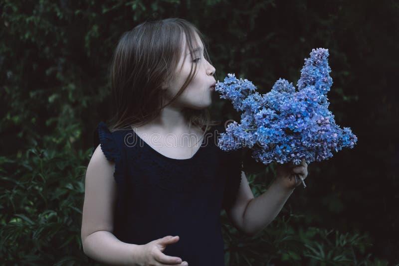 Petite fille mignonne embrassant le lilas photo libre de droits