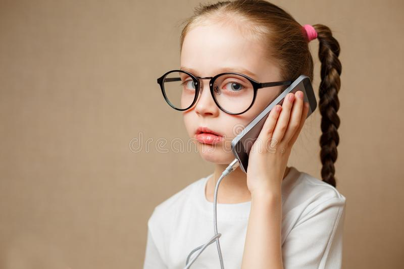 Petite fille mignonne employant Smartphone moderne photo stock