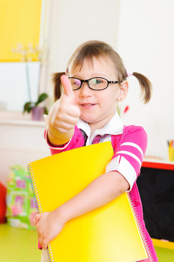 Petite fille mignonne en verres montrant le pouce  photo libre de droits