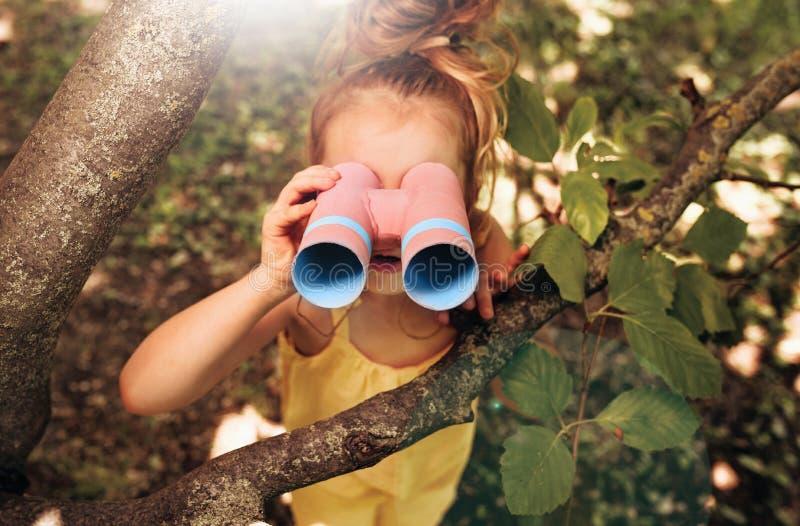 Petite fille mignonne et blonde à la recherche de jumelles à la recherche d'imagination ou d'exploration en été dans le parc Joye image libre de droits