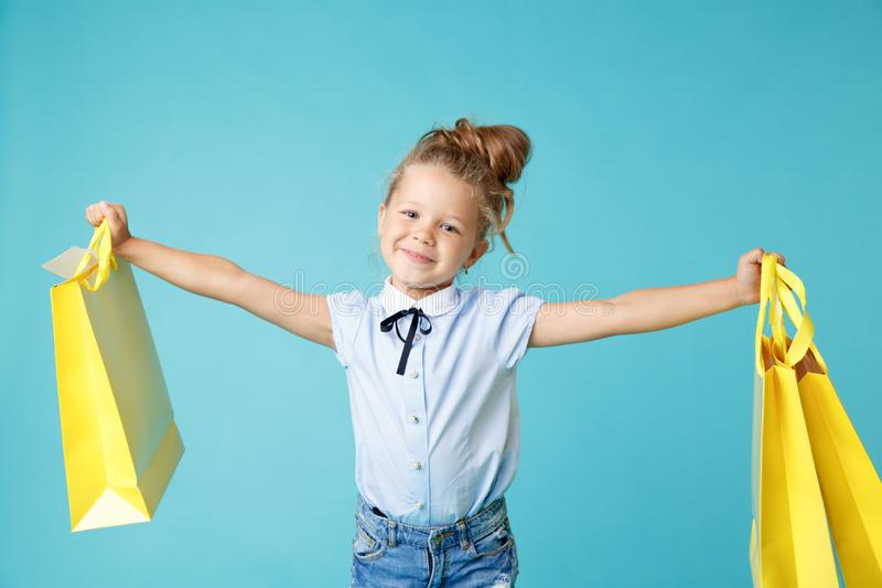 Petite fille mignonne et drôle tenant de grands sacs de papier jaune brillant dans le studio bleu photographie stock libre de droits