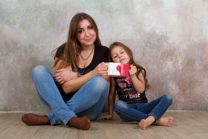 Petite fille mignonne et sa belle jeune mère s'asseyant ensemble sur le plancher photographie stock