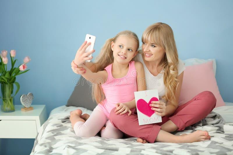 Petite fille mignonne et sa mère prenant le selfie avec la carte faite main dans la chambre à coucher photographie stock libre de droits