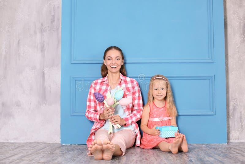 Petite fille mignonne et sa mère s'asseyant avec les fleurs et le boîte-cadeau sur le plancher à la maison C?l?bration du jour de photo libre de droits
