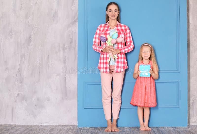 Petite fille mignonne et sa maman avec des cadeaux pour le jour de mère près du mur à la maison images libres de droits