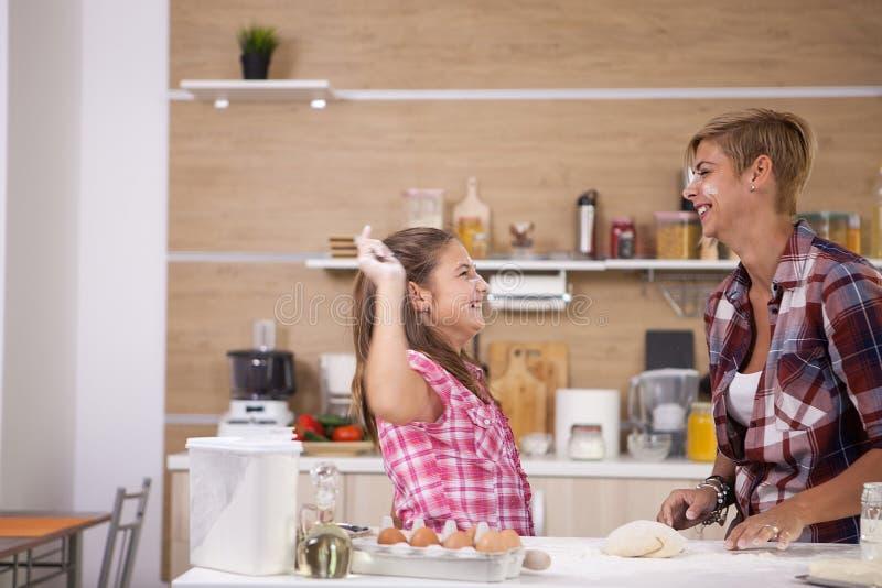 Petite fille mignonne faisant cuire avec sa nourriture saine de mère image stock